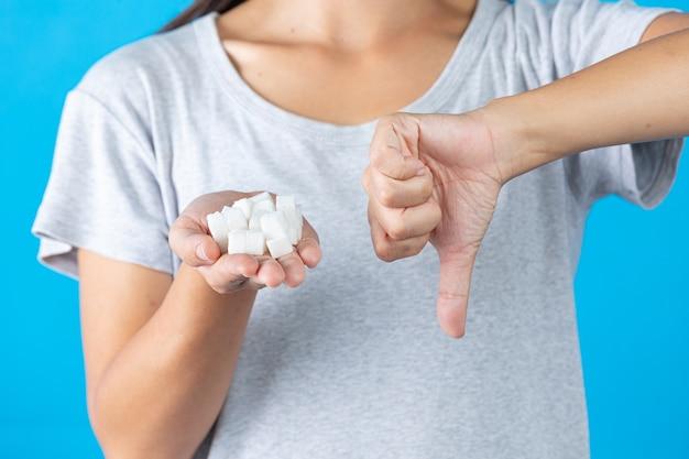 Всемирный день борьбы с диабетом; рука держит кубики сахара и большой палец в другой руке Бесплатные Фотографии