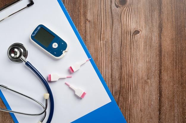 Giornata mondiale del diabete; attrezzature mediche sul pavimento in legno Foto Gratuite