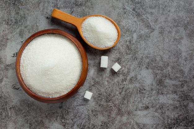 Giornata mondiale del diabete; zucchero in una ciotola di legno su sfondo scuro Foto Gratuite