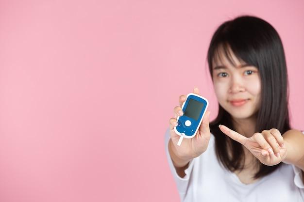 Всемирный день борьбы с диабетом; женщина, держащая глюкометр на розовой стене Бесплатные Фотографии
