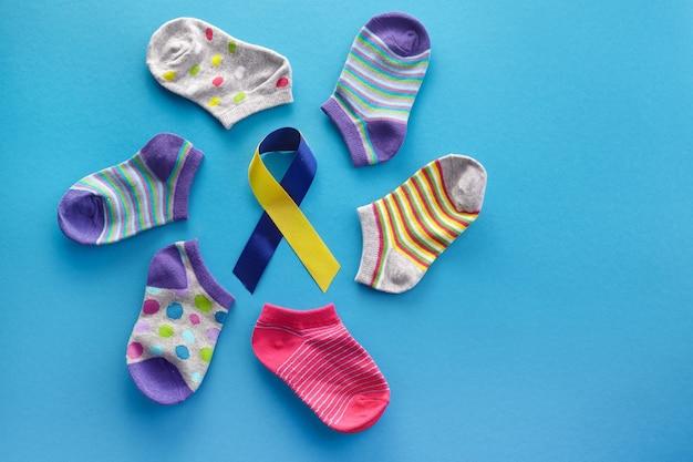 세계 다운 증후군의 날 배경. 다운 증후군 인식 개념. 양말과 파란색 배경에 리본 프리미엄 사진
