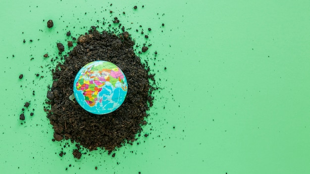 World environment day arrangement with globe and soil Premium Photo
