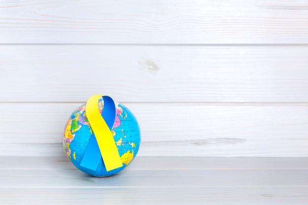 木製の背景に黄色と青のリボンと世界の地球。世界ダウン症の日のコンセプト。テキスト用のスペース。 Premium写真