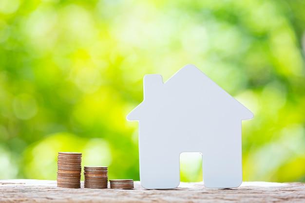 Giornata mondiale dell'habitat, immagine ravvicinata di una pila di monete e un modello di casa Foto Gratuite