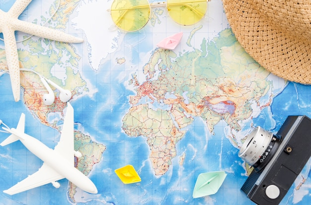 World map with camera, toy plane and starfish Free Photo