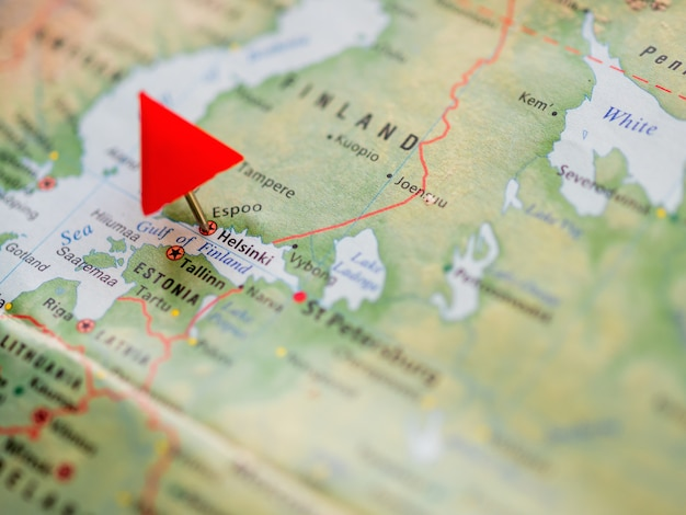 World map with focus on finland with red triangle pin on capital city helsinki. Premium Photo