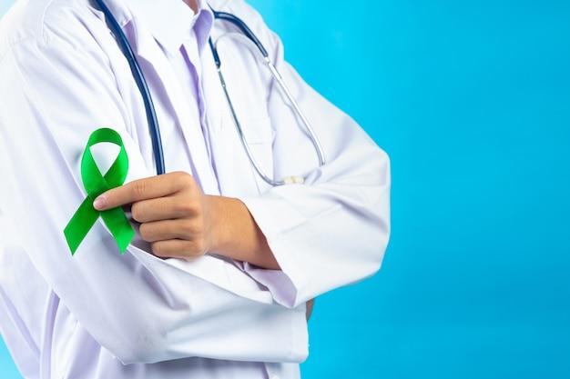 Giornata mondiale della salute mentale. mano del medico che tiene il nastro verde Foto Gratuite