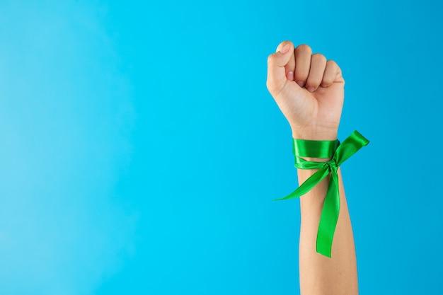 Giornata mondiale della salute mentale. nastri verdi legati al polso su sfondo blu Foto Gratuite