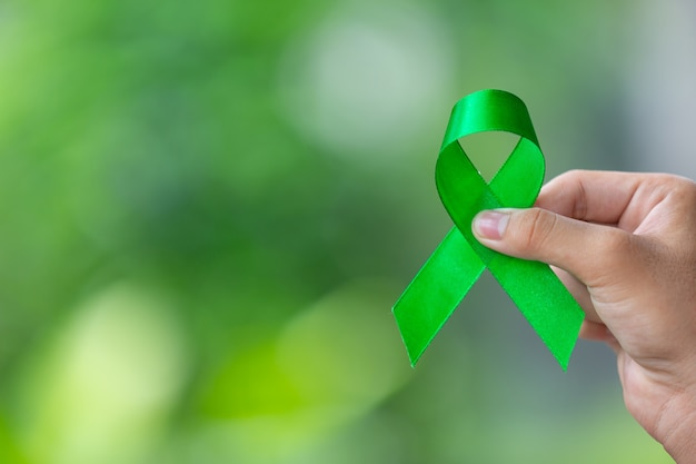 世界メンタルヘルスデー。緑のリボンを持っている手 無料写真