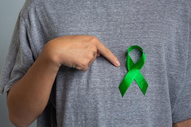 世界メンタルヘルスデー。緑のリボンを指す手 無料写真