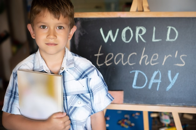 世界教師の日の挨拶、黒板の近くの生徒の男の子、チョークの碑文のテキスト Premium写真