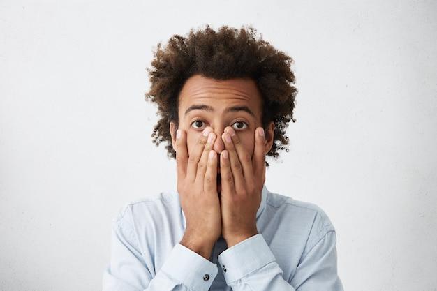 Обеспокоенный афро-американский бизнесмен, закрывающий лицо обеими руками Бесплатные Фотографии