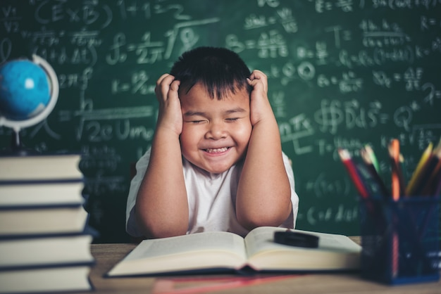Worried boy in classroom with hands on head Free Photo