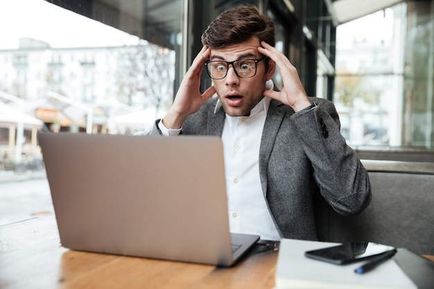 Worried confused businessman in eyeglasses sitting by the table in cafe while holding head and looking at laptop computer Free Photo