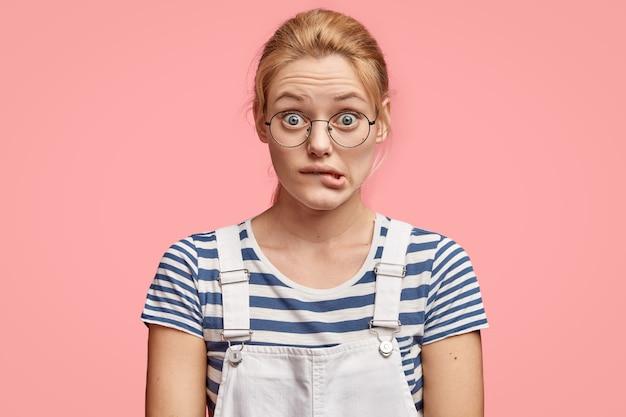 心配しているヨーロッパの女性は下唇を噛み、困惑した表情で見え、ファッショナブルな服を着て、ピンクの壁に立ちます 無料写真