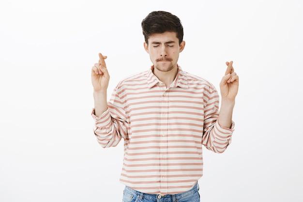 Встревоженный сосредоточенный привлекательный бородатый парень в полосатой рубашке, поднимающий скрещенные руки и закрывающий глаза, облизывающий губы от нервозности, надежды или желания, молящийся богу на удачу над серой стеной Бесплатные Фотографии