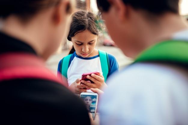 Worried girl standing between friends and using smart phone Premium Photo