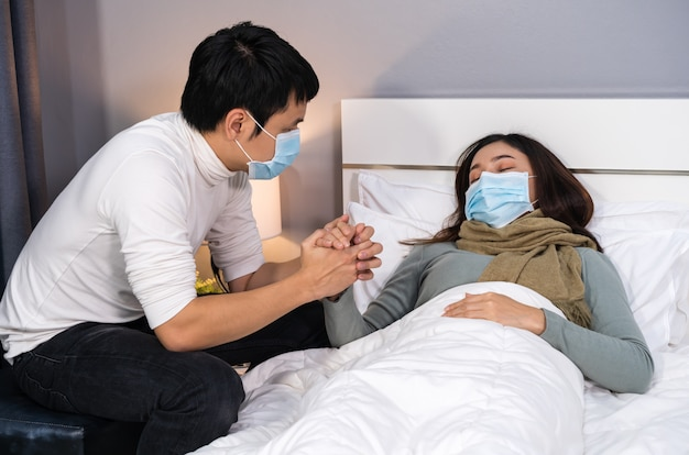 Взволнованный муж заботится о своей больной жене, пока она спит на кровати дома, люди должны быть в медицинской маске, защищающей от пандемии коронавируса Premium Фотографии