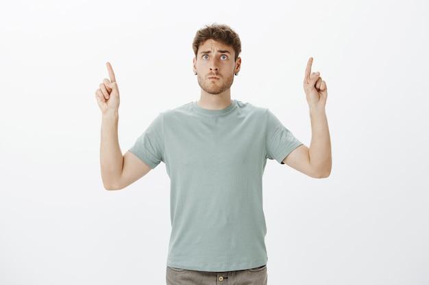 Обеспокоенный напряженный веселый светловолосый парень в футболке, показывающий вверх поднятыми указательными пальцами и смотрящий на небо с тревожно-испуганным выражением лица, беспокоясь за ребенка на детской площадке Бесплатные Фотографии