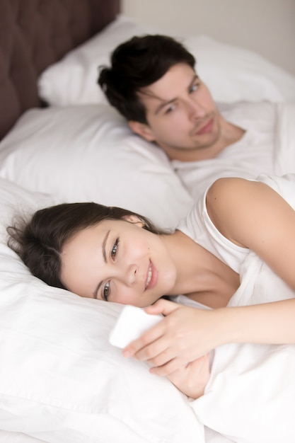 Worried man suspecting his girlfriend cheating using cellphone i Free Photo
