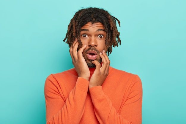 Worried man with dreadlocks, awaits nervously, keeps both palms on cheeks, gasps from fear, wears orange sweater Free Photo