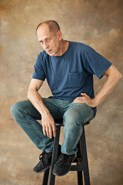 Взволнованный зрелый человек сидит в студии Бесплатные Фотографии