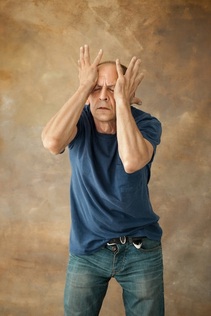 Worried mature man touching his head and thinking on. Free Photo