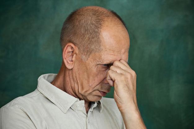 Worried mature man touching his head. Free Photo