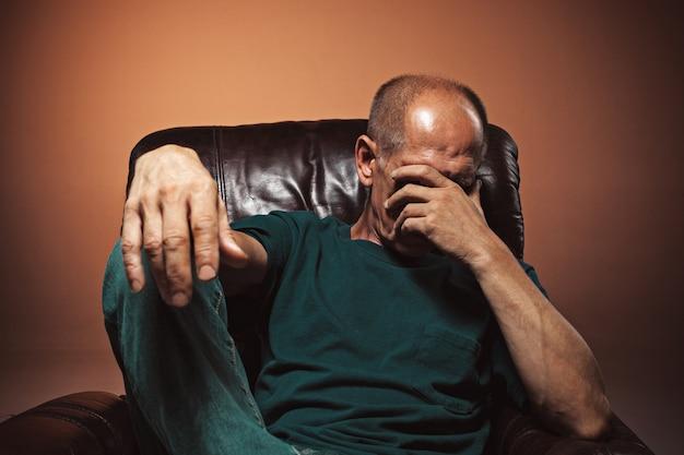 Обеспокоенный зрелый мужчина, касаясь его головы. Бесплатные Фотографии
