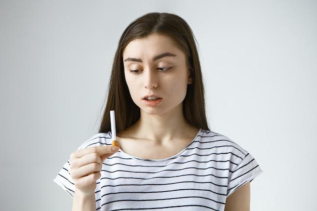 담배를 들고 캐주얼 티셔츠를 입고 걱정 당황한 젊은 갈색 머리 여성 무료 사진