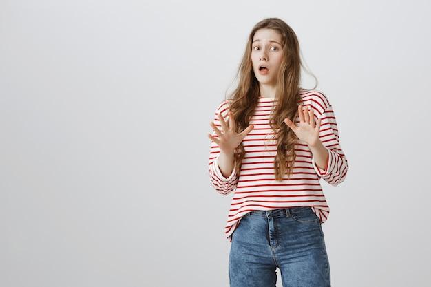 Обеспокоенная испуганная девушка поднимает руки вверх и испуганно отступает Бесплатные Фотографии
