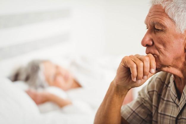 Worried senior man sitting on bed in bedroom Premium Photo