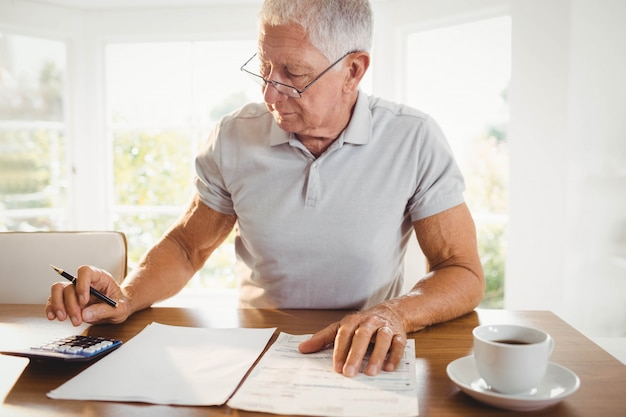 Worried senior man with tax documents at home Premium Photo