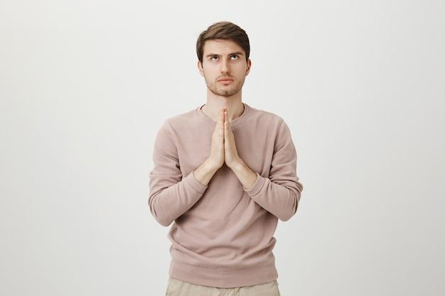 Uomo preoccupato dall'aspetto serio che prega dio, si tiene per mano in segno di supplica e guarda in alto Foto Gratuite