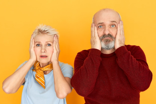 Обеспокоенная несчастная зрелая женщина и лысый небритый пожилой мужчина держатся руками за щеки, удивившись шокированным взглядам Бесплатные Фотографии