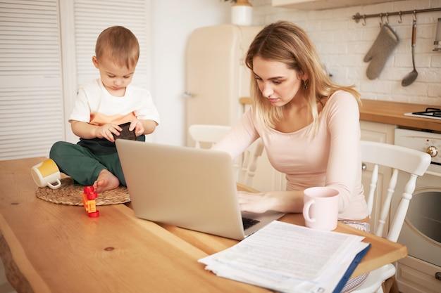 Preoccupato sconvolto giovane femmina bionda seduta al tavolo della cucina con documenti e computer portatile che si sente stressato perché deve fare rapporto e prendersi cura di suo figlio bambino mentre è a casa Foto Gratuite