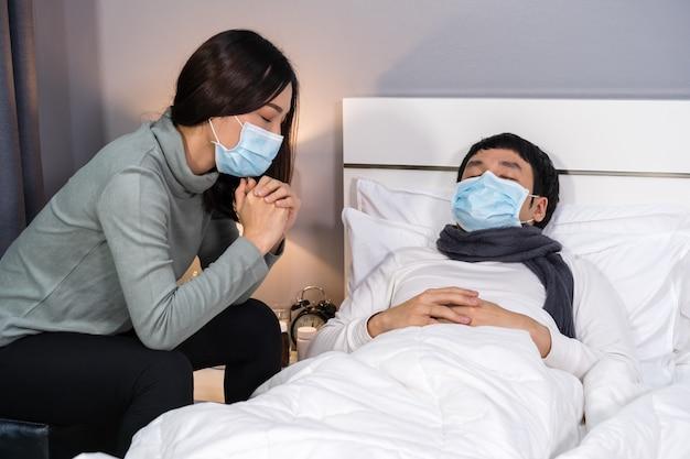 Взволнованная жена заботится о своем больном муже, пока он спит на кровати дома, люди должны быть в медицинской маске, защищающей от пандемии коронавируса Premium Фотографии