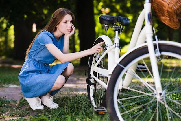 Worried woman checking her bike Free Photo