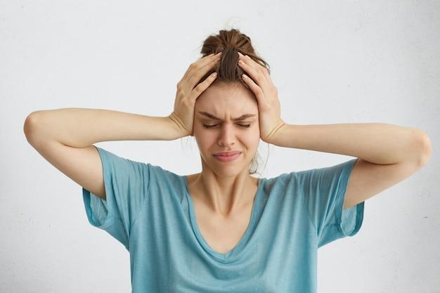 Взволнованная женщина, закрывая глаза, держась за голову с головной болью Бесплатные Фотографии