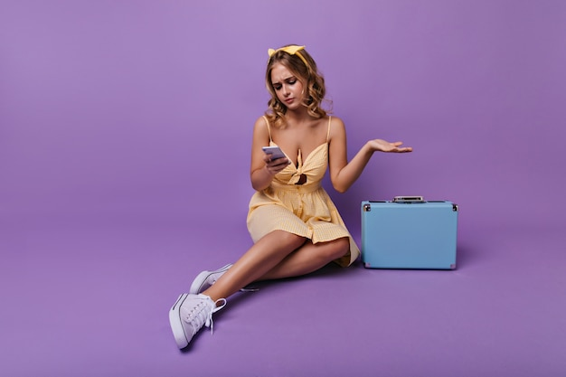 Donna preoccupata che si siede sul pavimento con il telefono. viaggiatore femminile in posa accanto alla valigia. Foto Gratuite