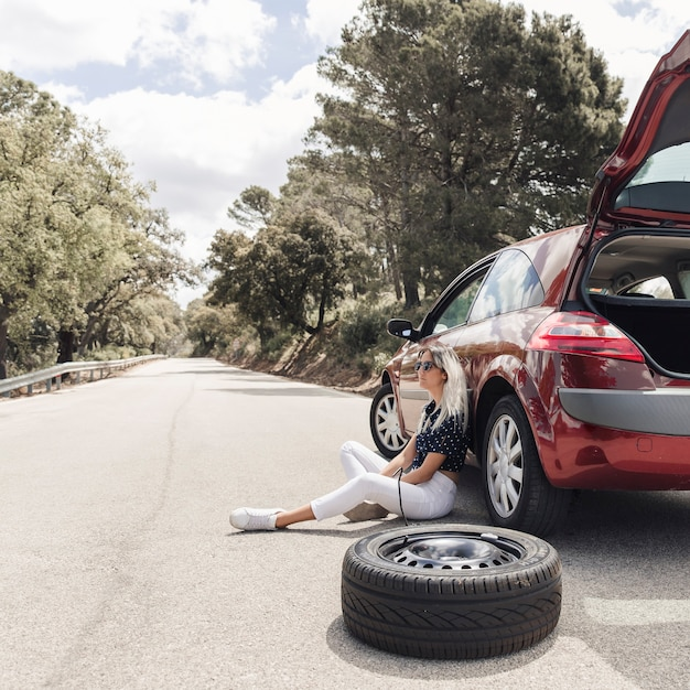 Worried young woman sitting near the broken down car on an empty road Free Photo