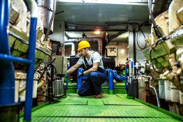 Worthy caucasian mechanic in overalls and with helmet kneeling inside ship and repairing engine. Premium Photo