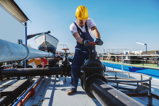 Worthy caucasian workman in overalls and with helmet on head standing on tanker and screwing the valve. Premium Photo