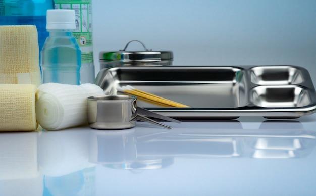 創傷ケアドレッシングセットとステンレススチールプレート、鉗子、ヨウ素カップ、適合包帯、弾性凝集保持包帯、防腐剤および生理食塩水ボトル、器具容器。医療用品。 Premium写真