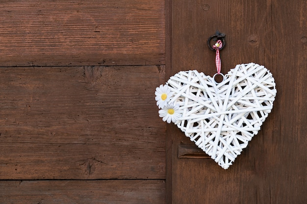 A woven white heart with daisies hangs on a wooden wall. Premium Photo