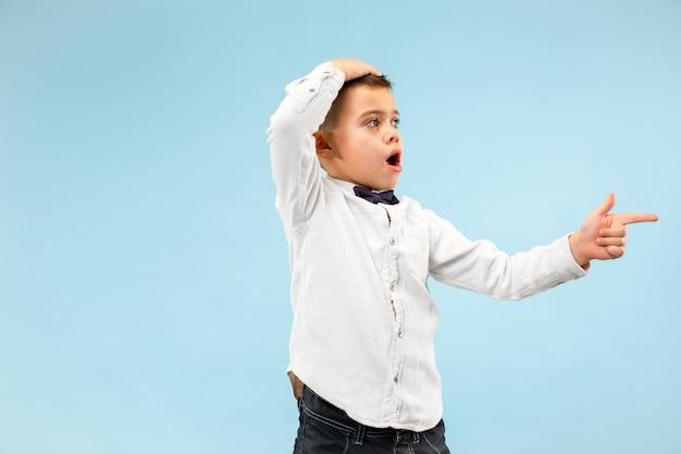 Wow. ritratto frontale a mezzo busto maschio attraente sul backgroud blu dello studio. giovane ragazzo teenager sorpreso emotivo in piedi con la bocca aperta. emozioni umane, concetto di espressione facciale. colori alla moda Foto Gratuite