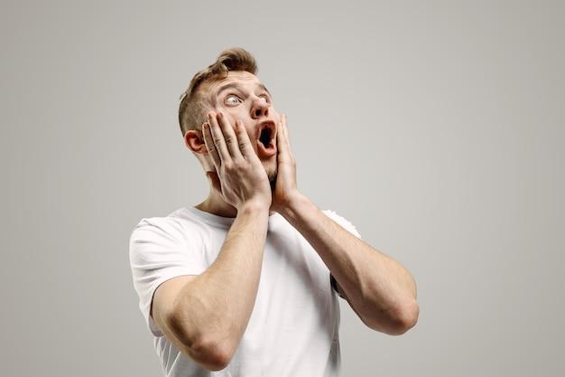 ワオ。灰色のスタジオの背景に魅力的な男性のハーフレングスの正面の肖像画。口を開けて立っている若い感情的な驚きのひげを生やした男。人間の感情、表情の概念 | 無料の写真