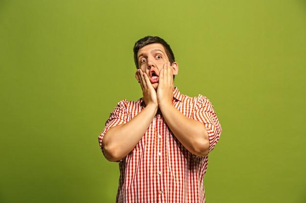 Ух ты. привлекательный мужской пояс передний портрет на зеленом backgroud студии. молодой эмоциональный удивленный бородатый мужчина, стоя с открытым ртом. человеческие эмоции, концепция выражения лица. модные цвета Бесплатные Фотографии