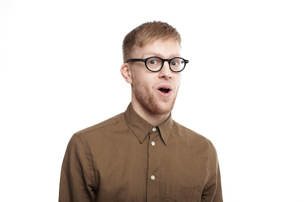 Wow. handsome emotional hipster guy in stylish eyewear staring in full disbelief, raising brows and opening mouth, having completely shocked expression on his hairy face Free Photo