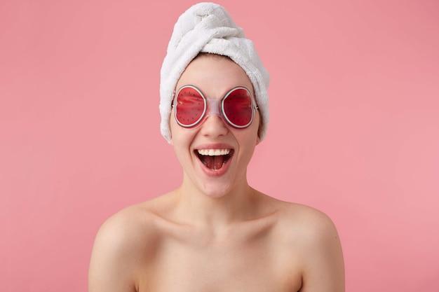 うわー!とてもクール!目の上にスパマスクを置き、頭にタオルを置き、口と目を大きく開いた後の若い幸せな驚きの女性は、クールなニュースを聞いて立っています。 無料写真